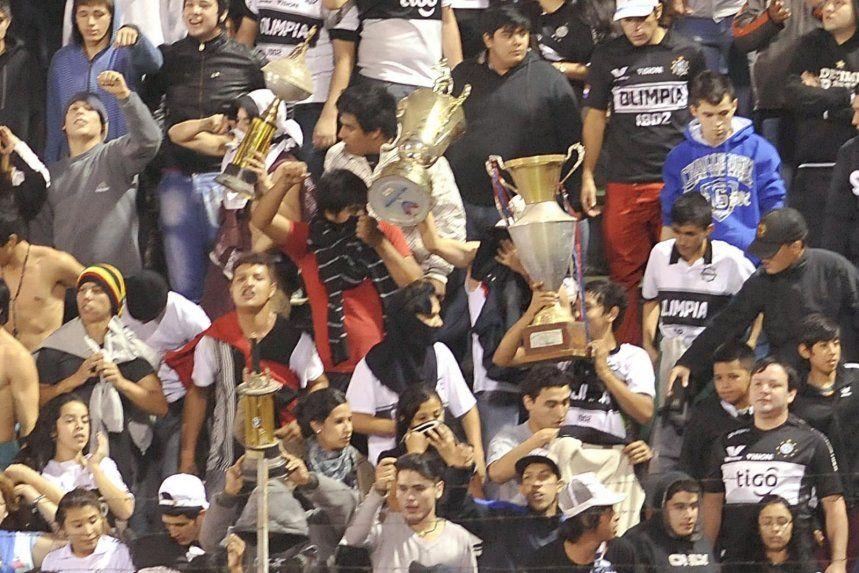 http://www.lavozdigital.com.py//assets/hinchas-de-olimpia-presumen-de-las-copas-que-robaron-del-museo-de-guarani-_859_573_1237349.JPG